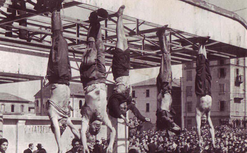 Il cadavere di Mussolini assieme a quelli di Claretta Petacci e di altri gerarchi fascisti fucilati esposti a testa in giù in Piazzale Loreto, a Milano