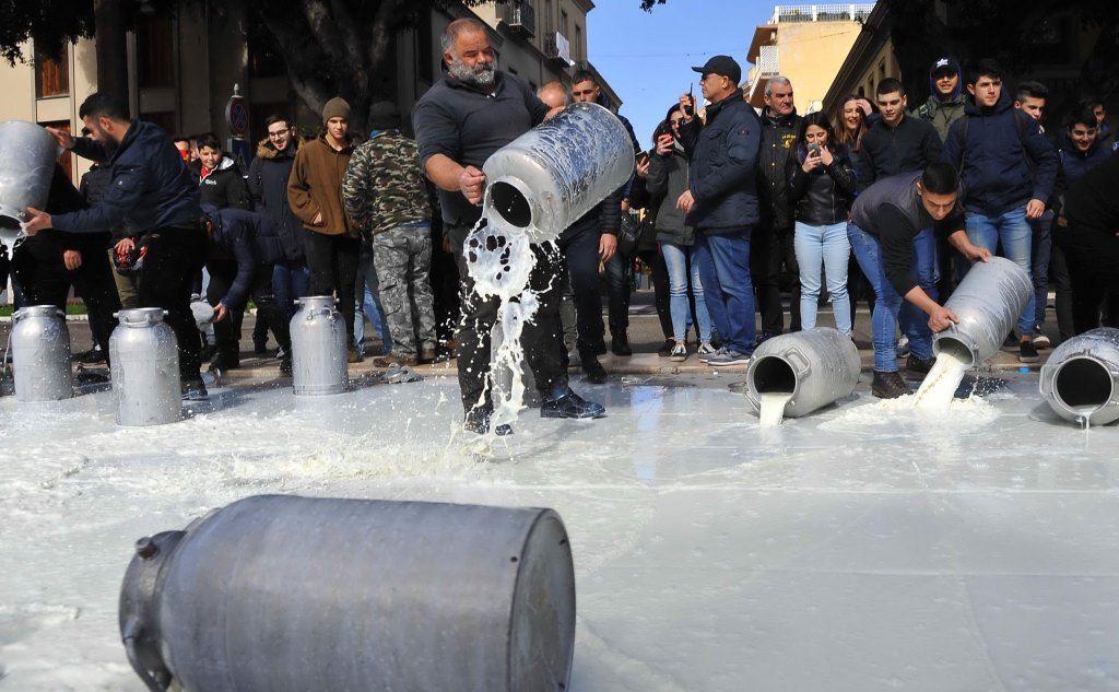 Pastori gettano latte nella fontana di piazza Roma, a Oristano