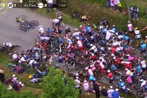Tour de France, il cartello di una spettatrice in mezzo alla strada causa maxi caduta di gruppo