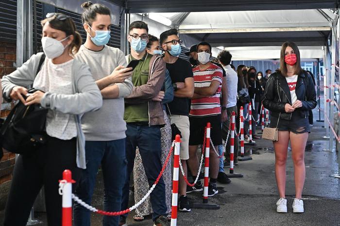 Giovani in coda in attesa del vaccino (foto Ansa)