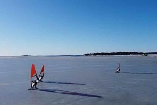 Il nuovo sport, appassionati di windsurf sfrecciano sul mare ghiacciato