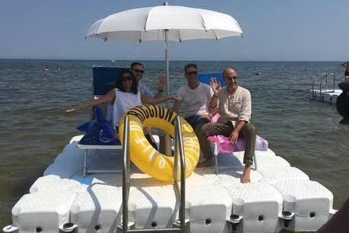 """Poco spazio in spiaggia? A Riccione gli ombrelloni si """"piantano"""" in mare"""
