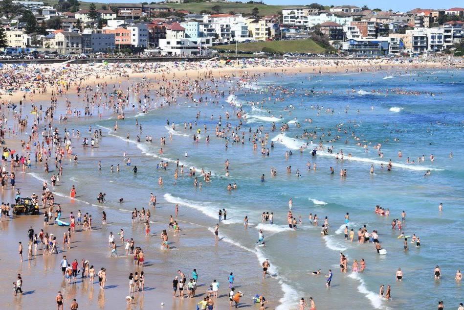La spiaggia di Sidney piena di turisti nel giorno di Natale (Ansa)