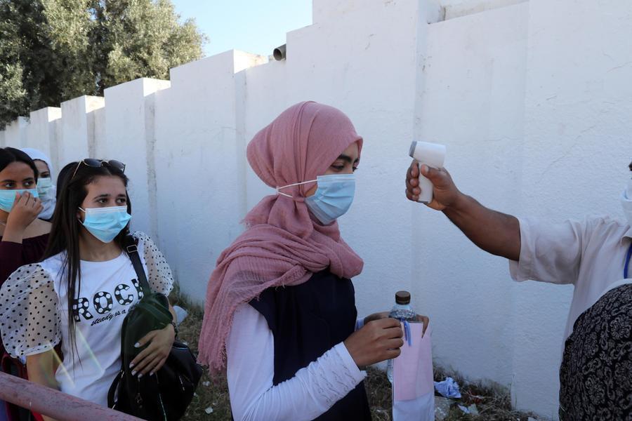 La misurazione della temperatura in una scuola tunisina (Ansa)