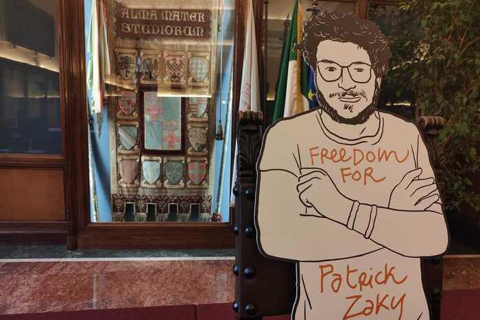 """Patrick Zaki """"si laurea""""a Bologna: la consegna del diploma al suo cartonato"""