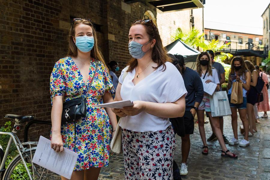 Due ragazze in coda davanti a un centro vaccinale di Londra (Ansa)