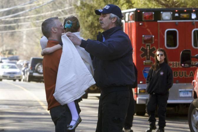 Una bimba portata in salva dalla scuola, dopo l'assalto del 2012 (Archivio L'Unione Sarda)