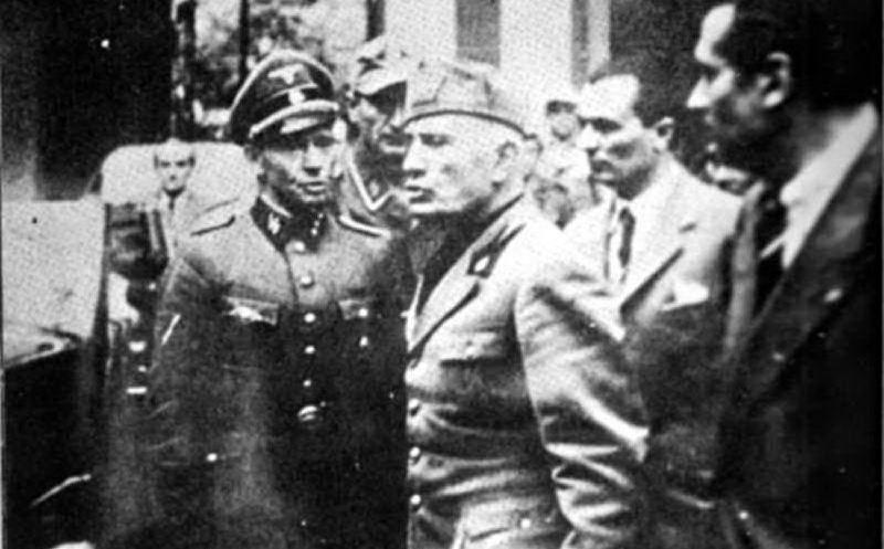 L'uiltima foto che lo ritrae da vivo, mentre lascia la Questura di Milano con un capo scorta delle SS